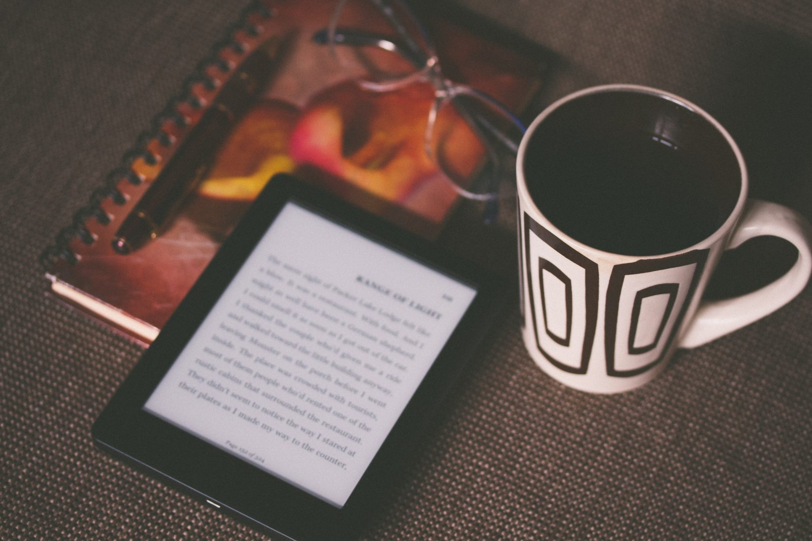An ereader and coffee on table next to a notebook and glasses