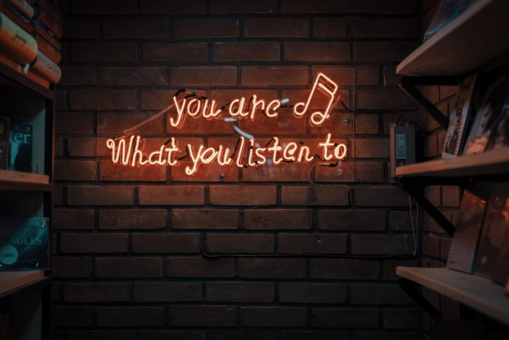A neon sign with a music note that says: you are what you listen to