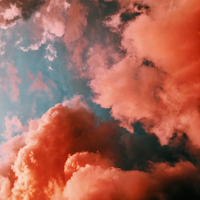 Fluffy clouds in peach, orange, and pink hues.