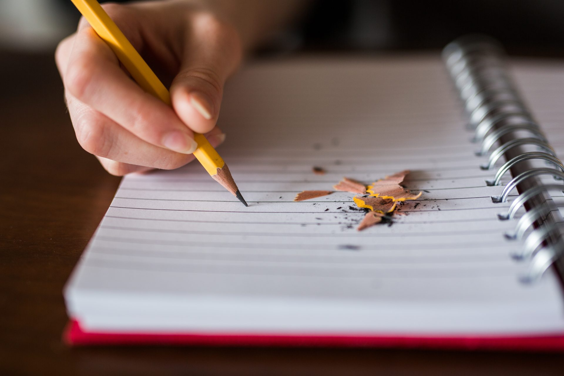 A person writing in a red lined notebook with a pencil, with pencil shavings on the paper.