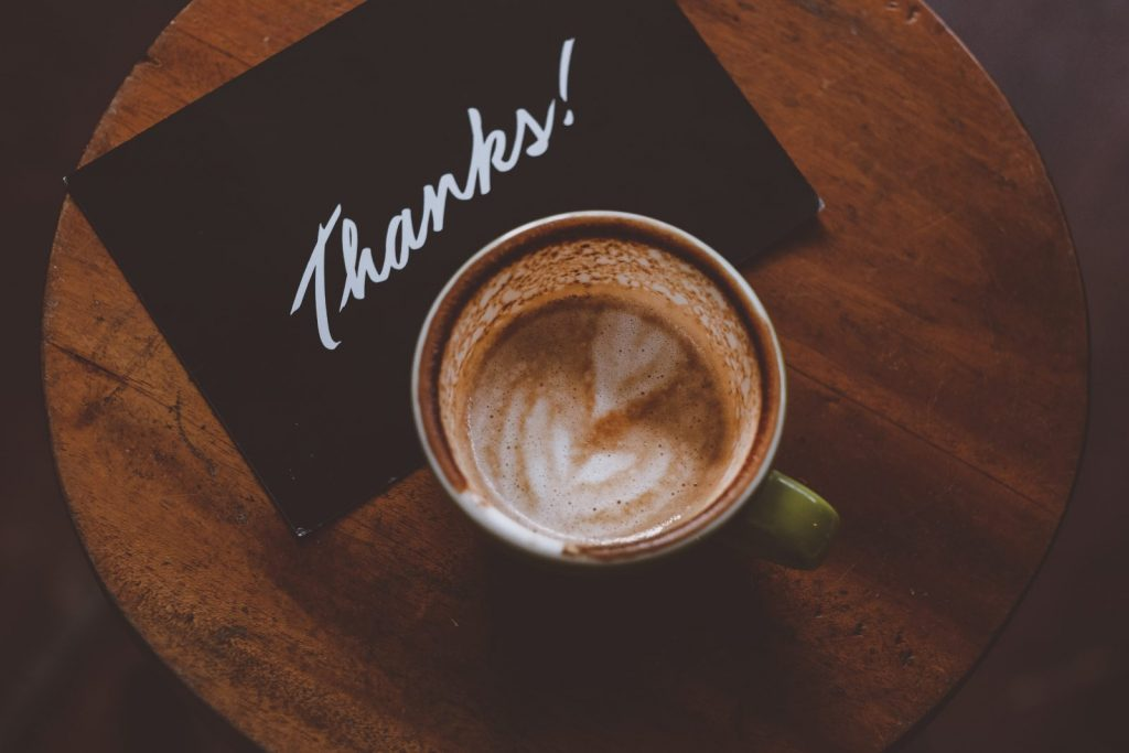 A coffee and a thank you card on a table.