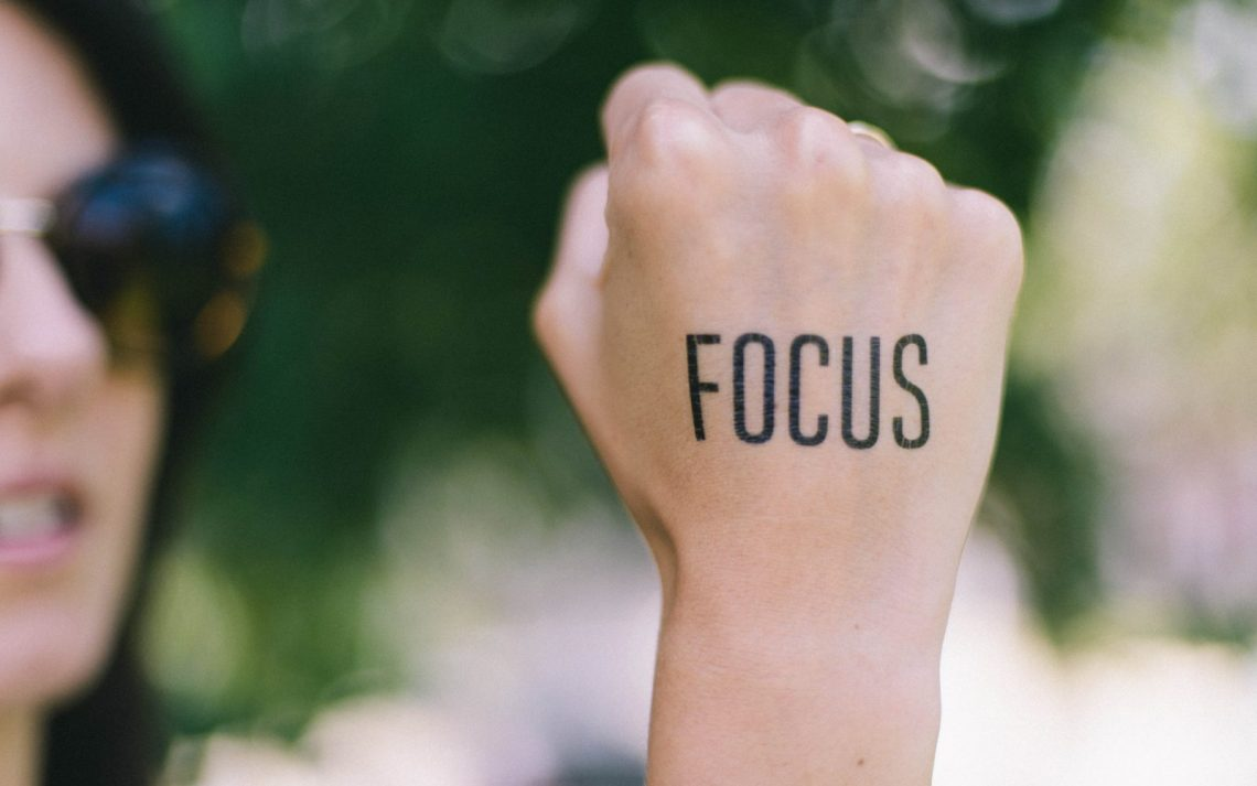 "The word ""focus"" written on the back of someone's fist, with the background blurred."