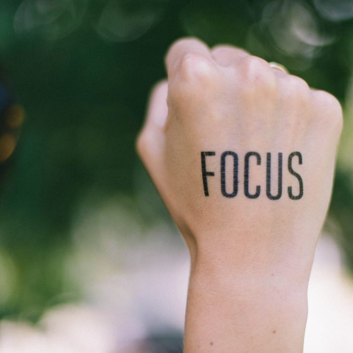 """The word """"focus"""" written on the back of someone's fist, with the background blurred."""