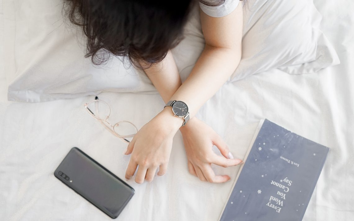 "A person sits on a bed with just their arms visible, crossed one over the other. They wear a watch, and one hand reaches to a phone face down on the blanket, the other to the book ""Every Word You Cannot Say"" by Iain S. Thomas. The colours are light, with the phone, book, person's hair, and an analog watch standing out in dark brown and grey."