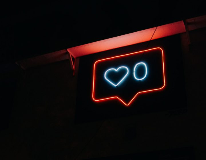 A neon sign that shows a 'like' button notification with a heart and the number zero.
